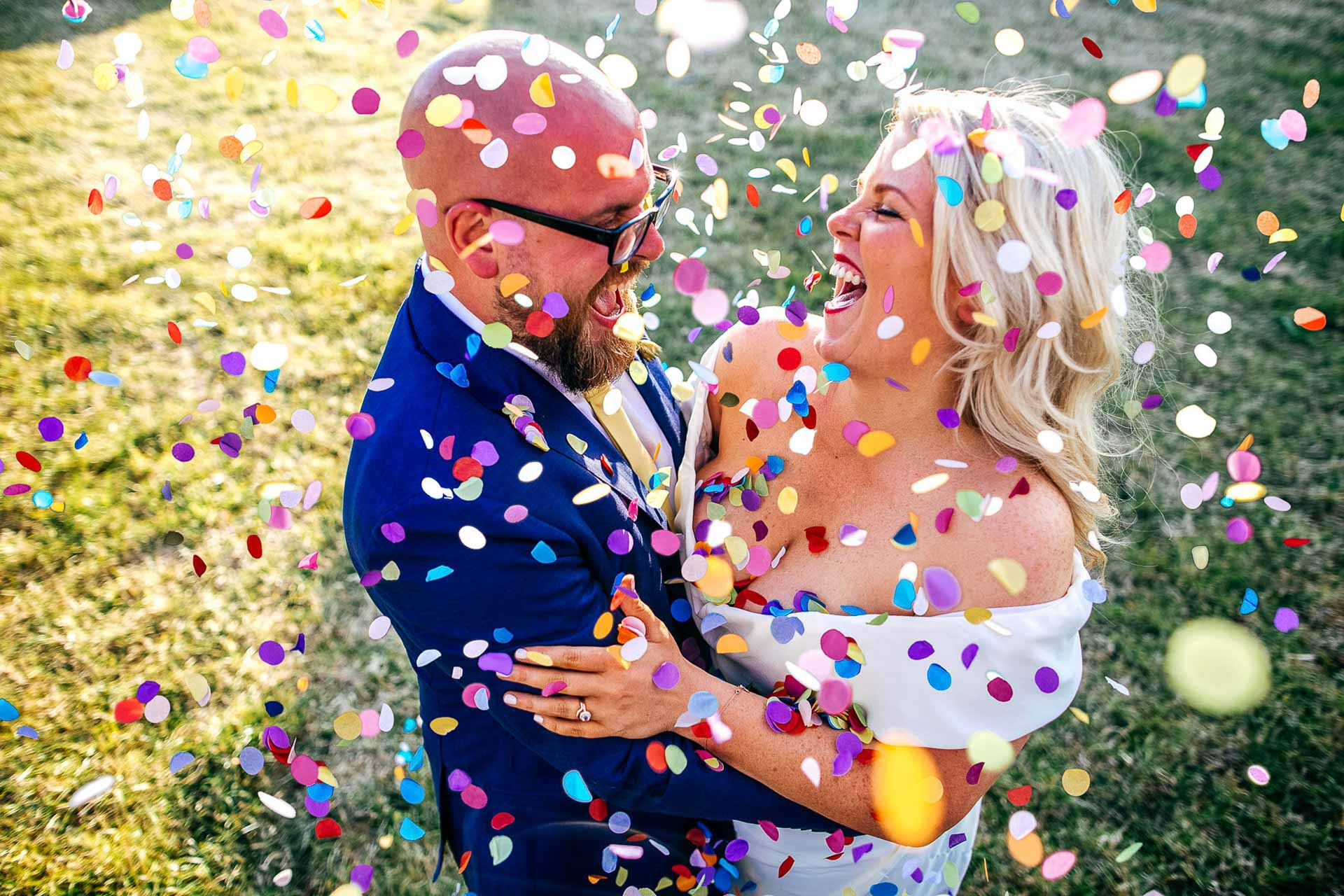 Bride and Groom embrace under lots of colourful confetti at Maplehurst Farm Horsham