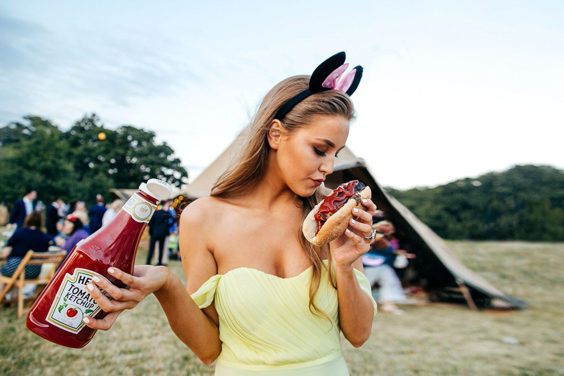 Image os bridesmaid holding a hotdog provocatively at a Tipi Wedding