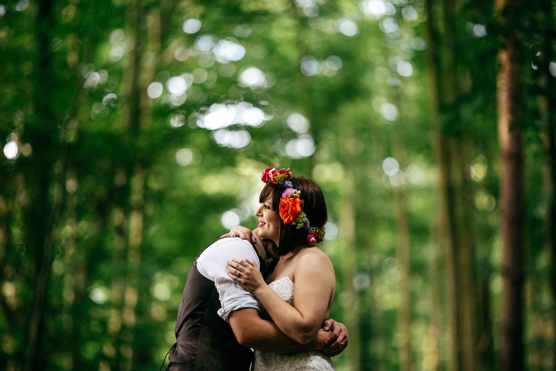 Newly married couple hug in woods at The Keeper and The Dell Boho Wedding in Norfolk