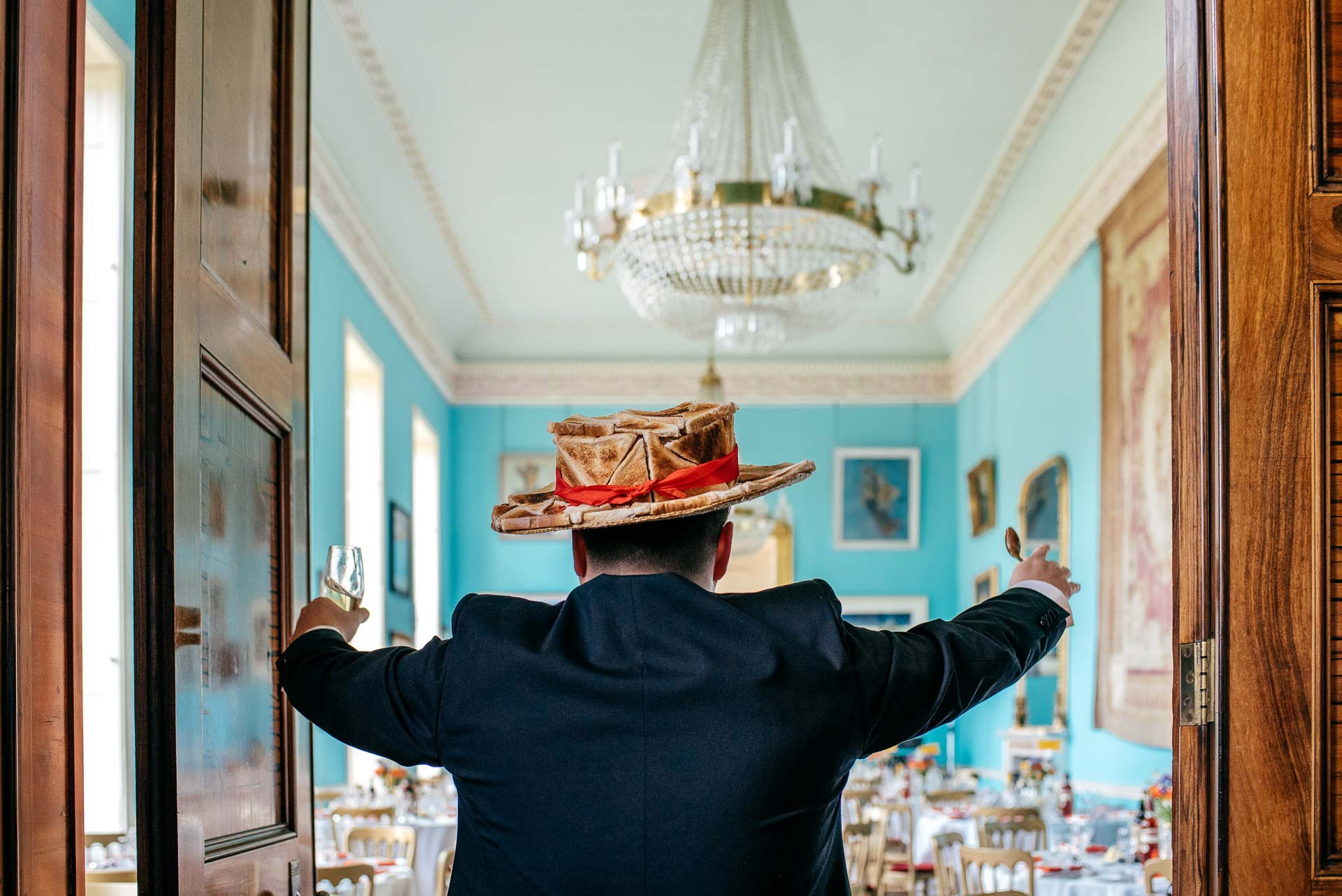 Toastmaster in a hat made of toast swings doors open of Walcot Hall to announce guests into the room
