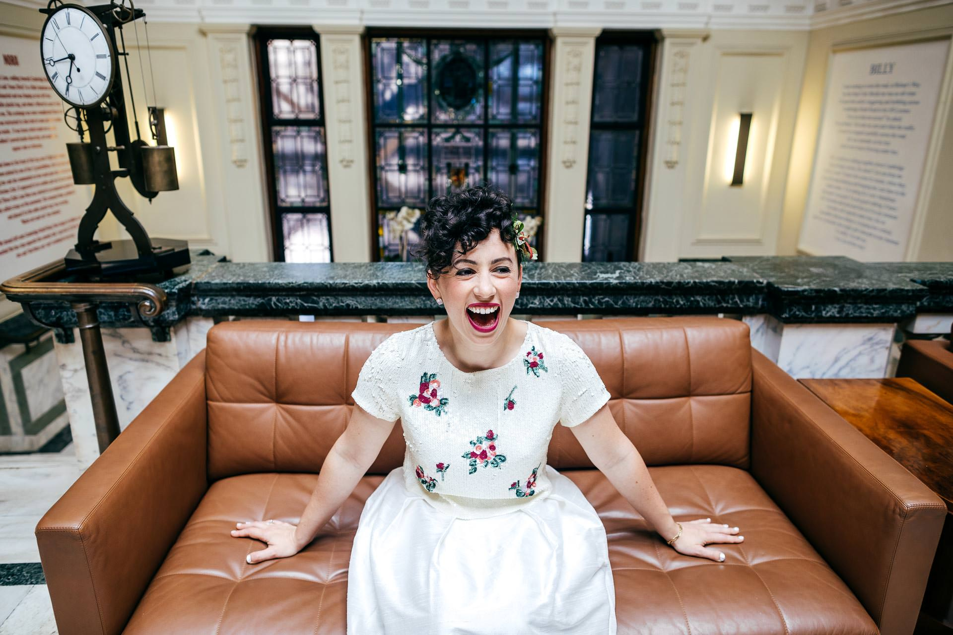 Jewish Bride looking super happy pre ceremony at The Town Hall Hotel London. Sat on sofa waiting to get married.