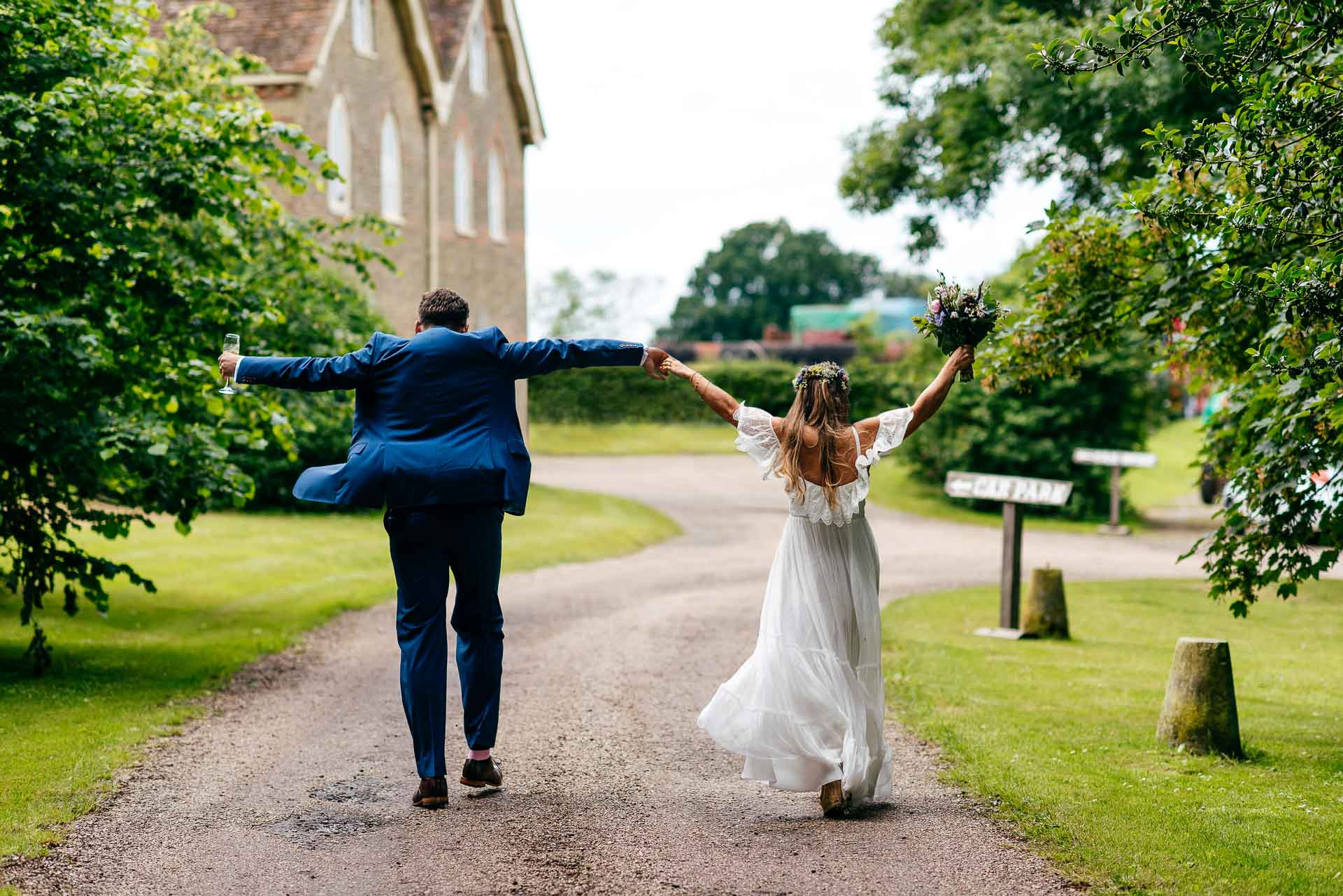 Bride and Groom celebrate quietly on their own as they emerge from the church and head down to the reception. Hand in hand arms aloft.