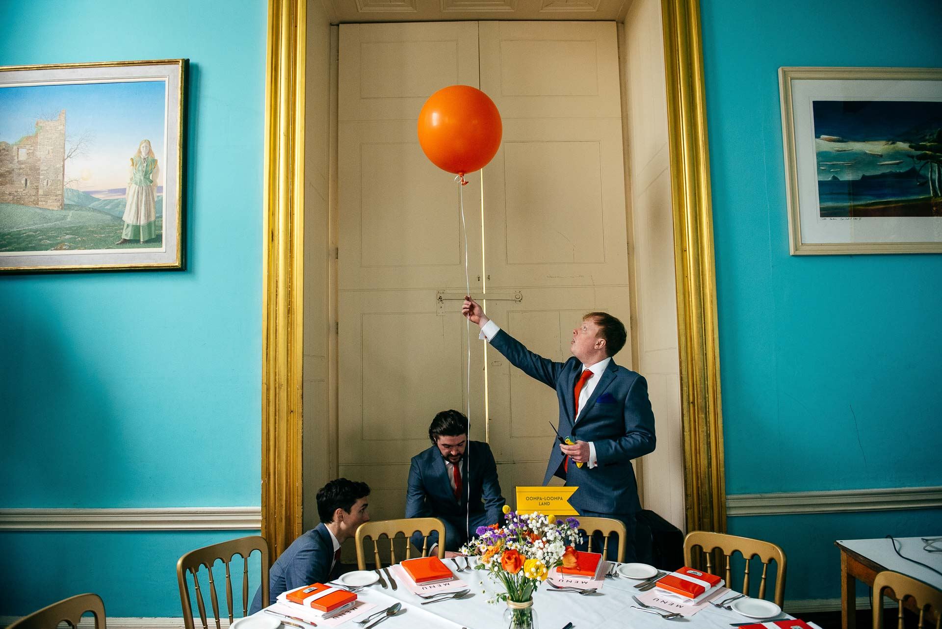 Ushers prepare the dining room at Walcot Hall Shropshire blowing up and placing balloons