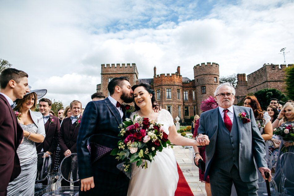 Father of the bride walks bride to groom at outdoors Rowton Castle Wedding