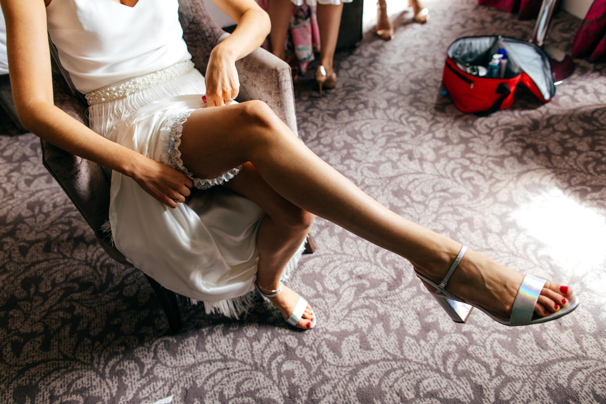 bride puts garter on long legs holographic shoes charlie bread tassel skirt