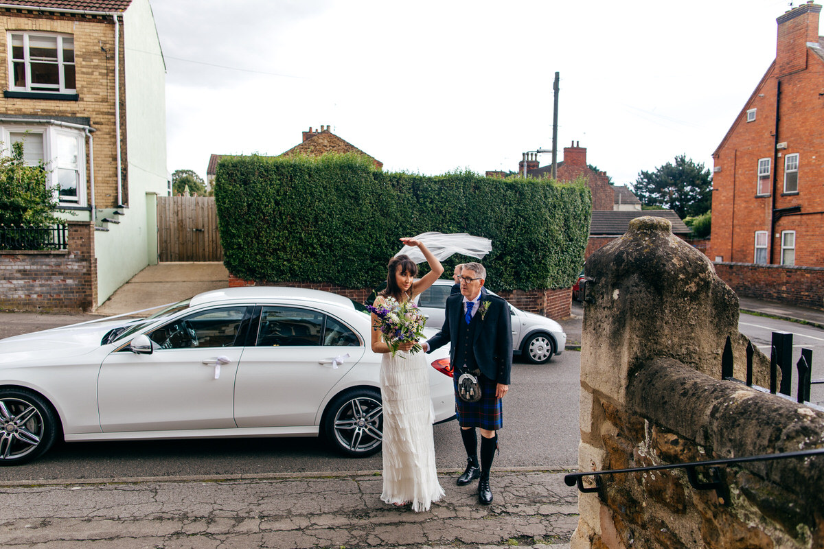 Bride arrives to church with dad in kilt veil bowing in the wind