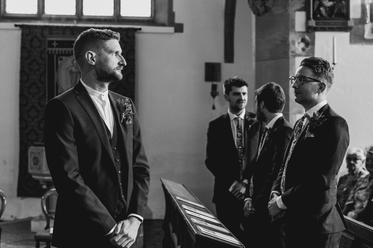 Groom waiting for bride to walk down the aisle best man looking on