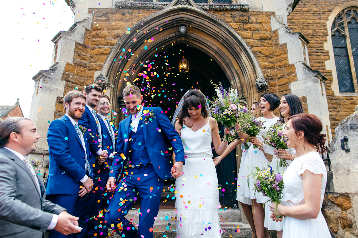 Charlie Brear Tassle Dress bride and groom in grandad collar suit leave church confetti in the air