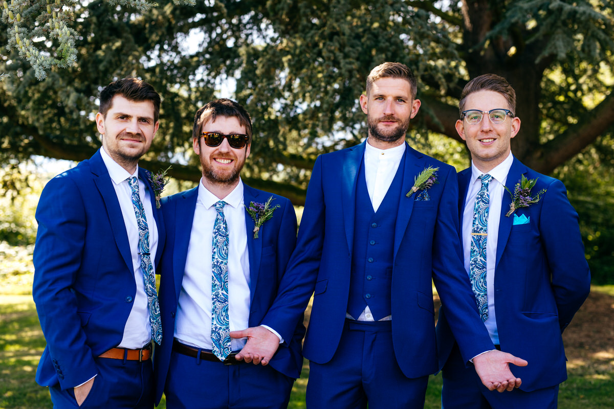 Grooms party wearing blue suits groom in mod grandad collar suit