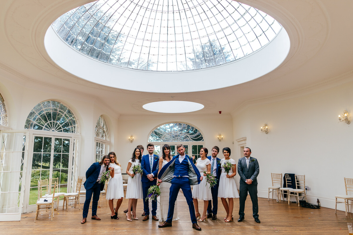 Sassy group shot at Barton Hall Wedding in Northamptonshire Bridal and Groom Party Groom holding his jacket open