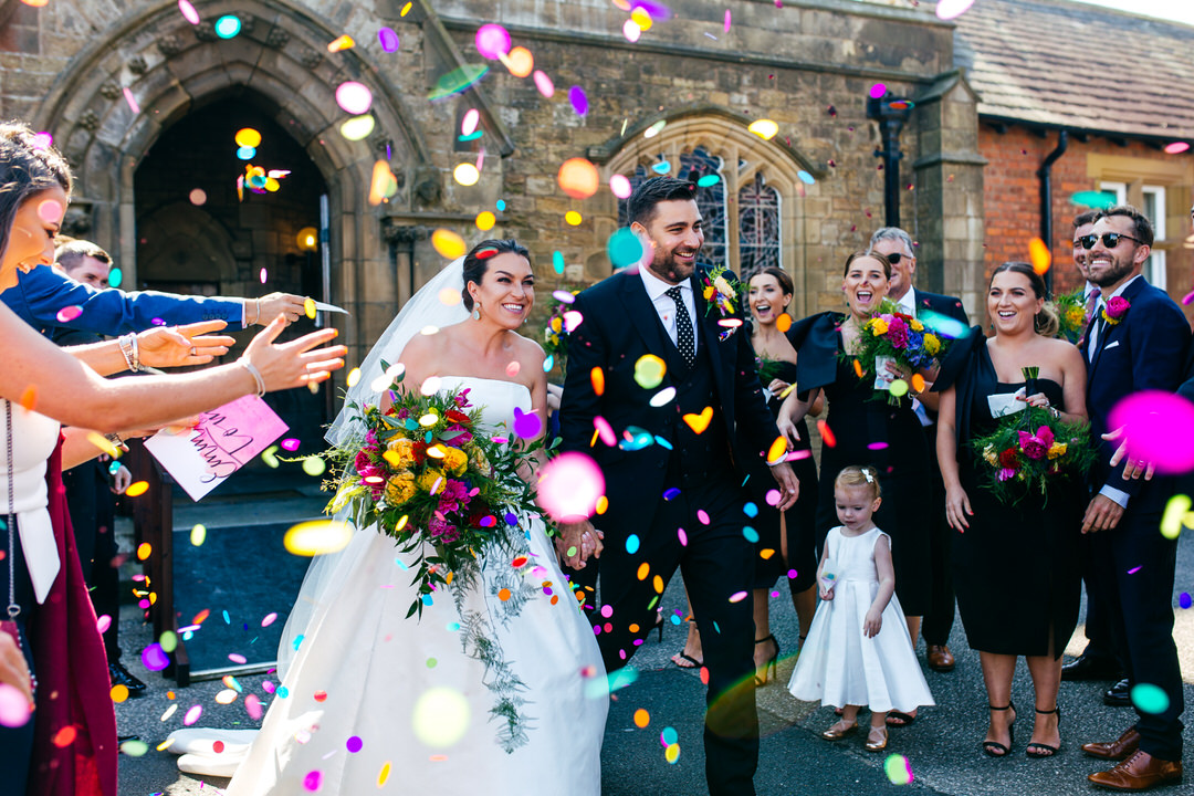 Colourful confetti exit for fun loving EMma and Tom from Rossall School Church