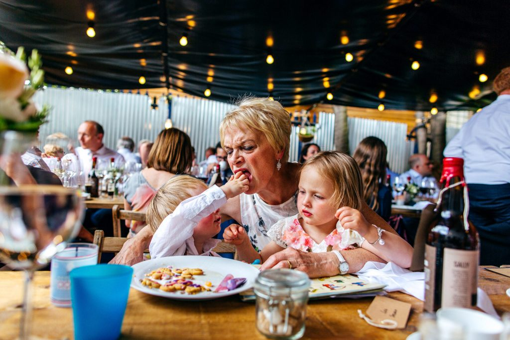 Twins forcefeeding their nan sweeties at wedding dinner table