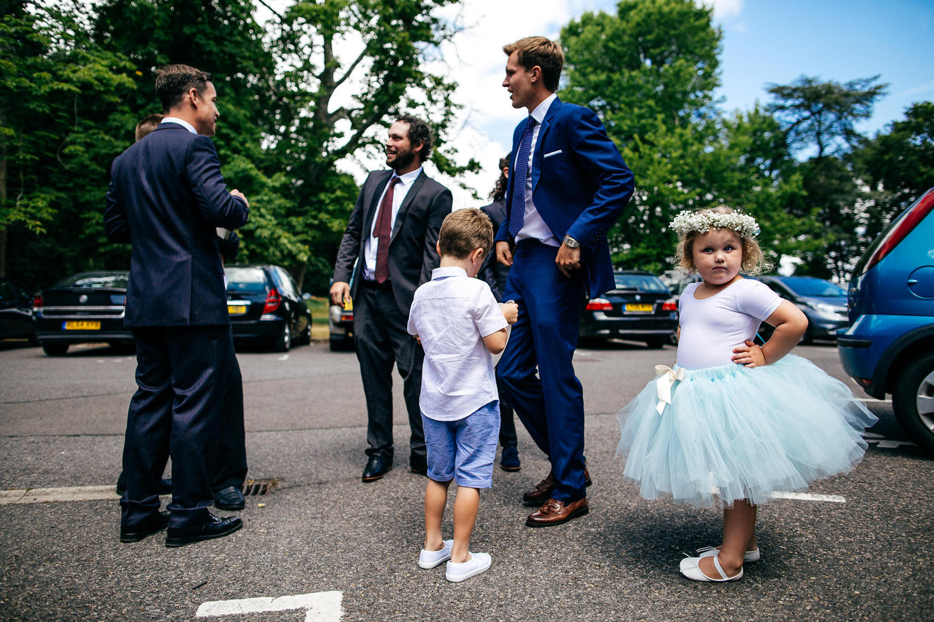 Flowergirl waits outside church in car park with hands on her hips looking straight down the camera.