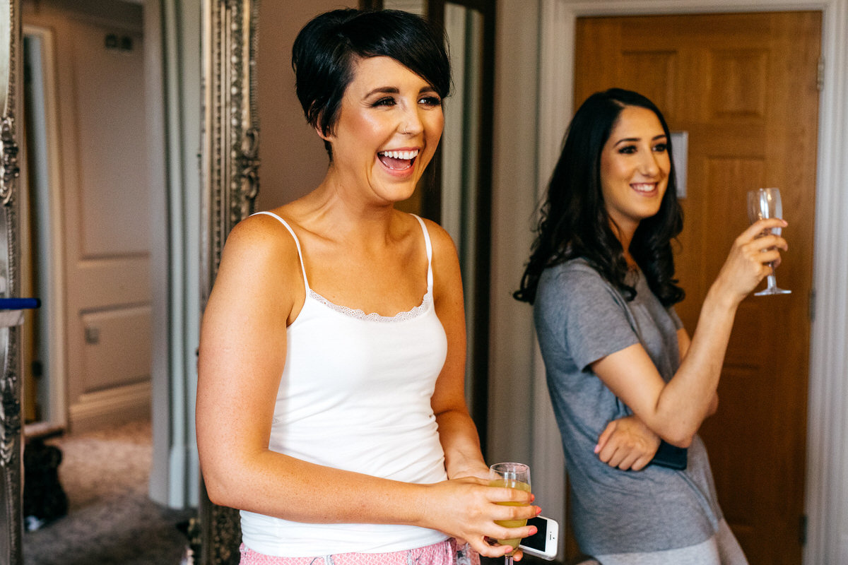 Bridesmaids drinking during bridal prep laughing