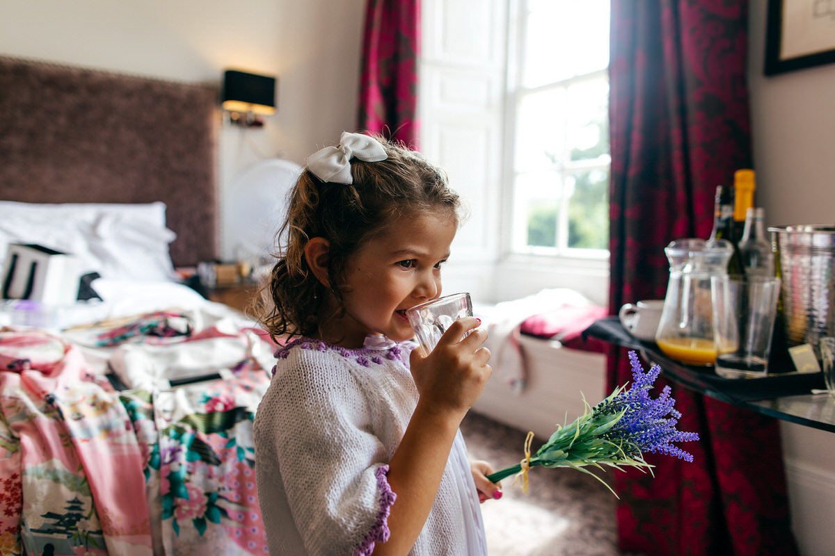 Flower girl drinking and smiling during bridal prep at Barton Hall Hotel
