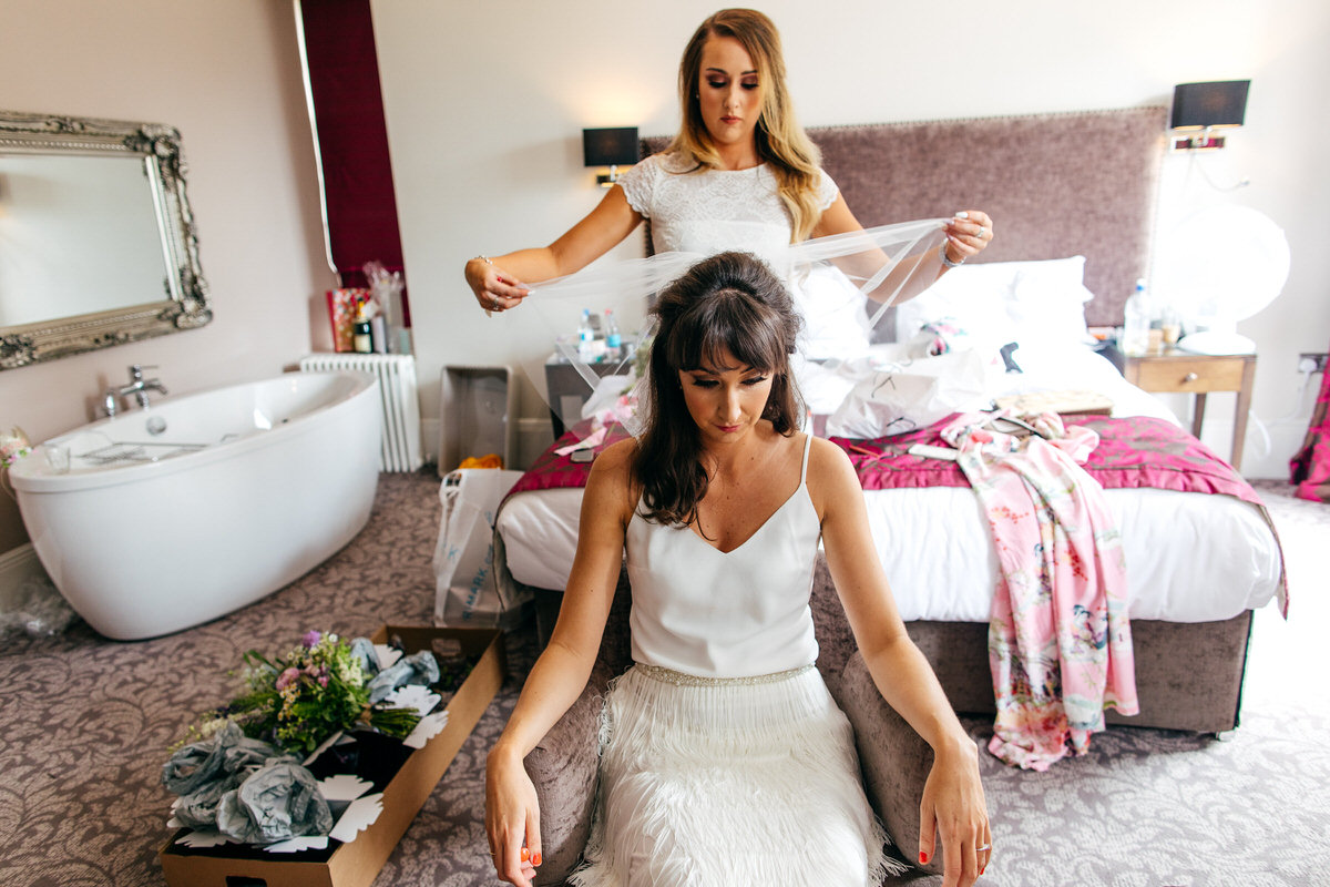 Bridesmaid puts on veil for bride wearing Charlie Brear in hotel room