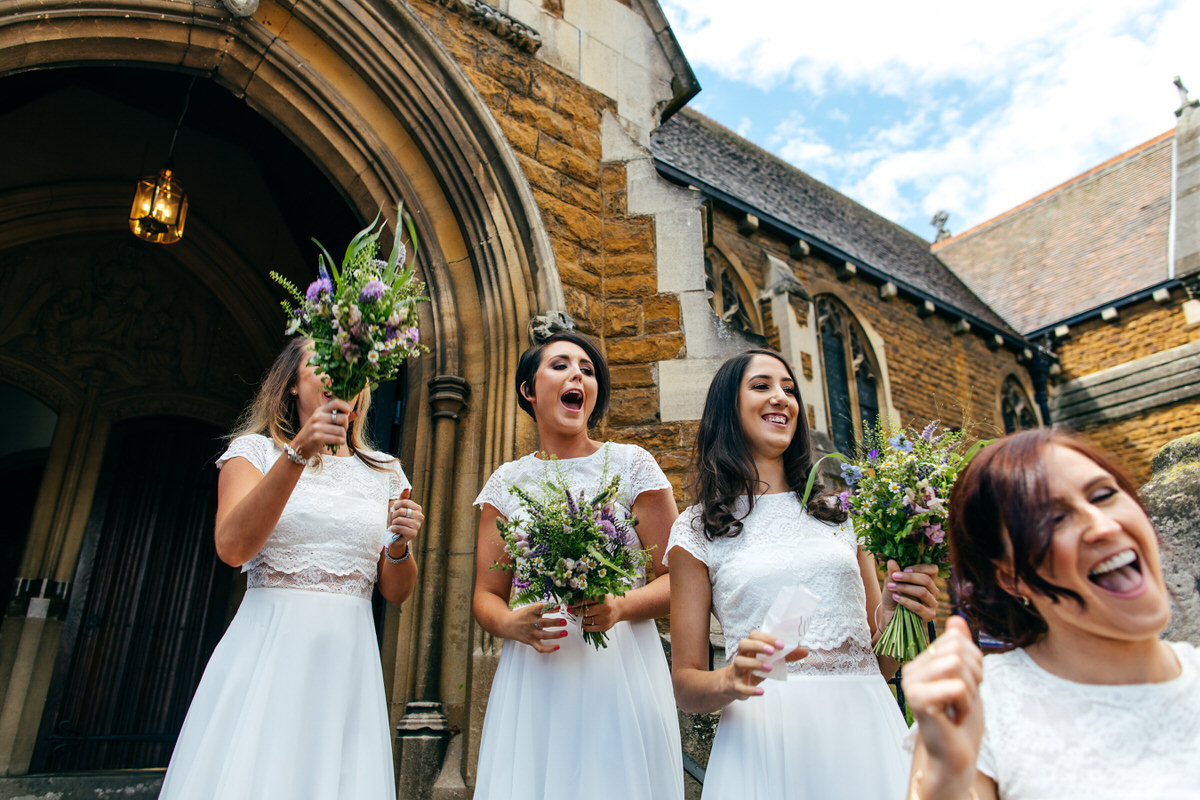 bridesmaids whooping after bride and groom exit church