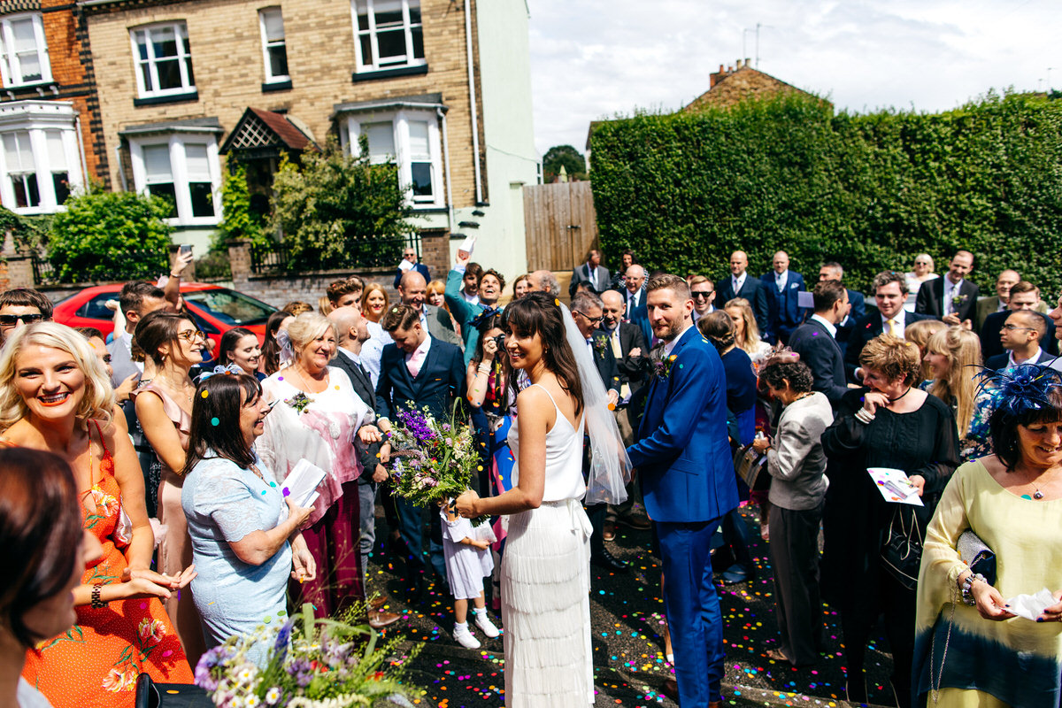 bride and groom surrounded by friends and family after confetti throw