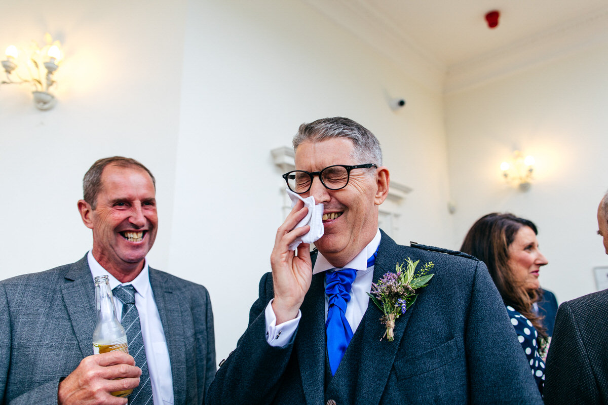 father of the bride laughing but pretending to cry at wedding reception