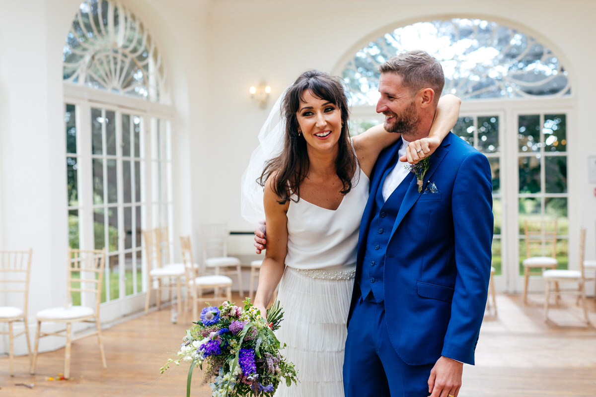 bride and groom hug in orangery at Barton Hall Wedding Northamptonshire