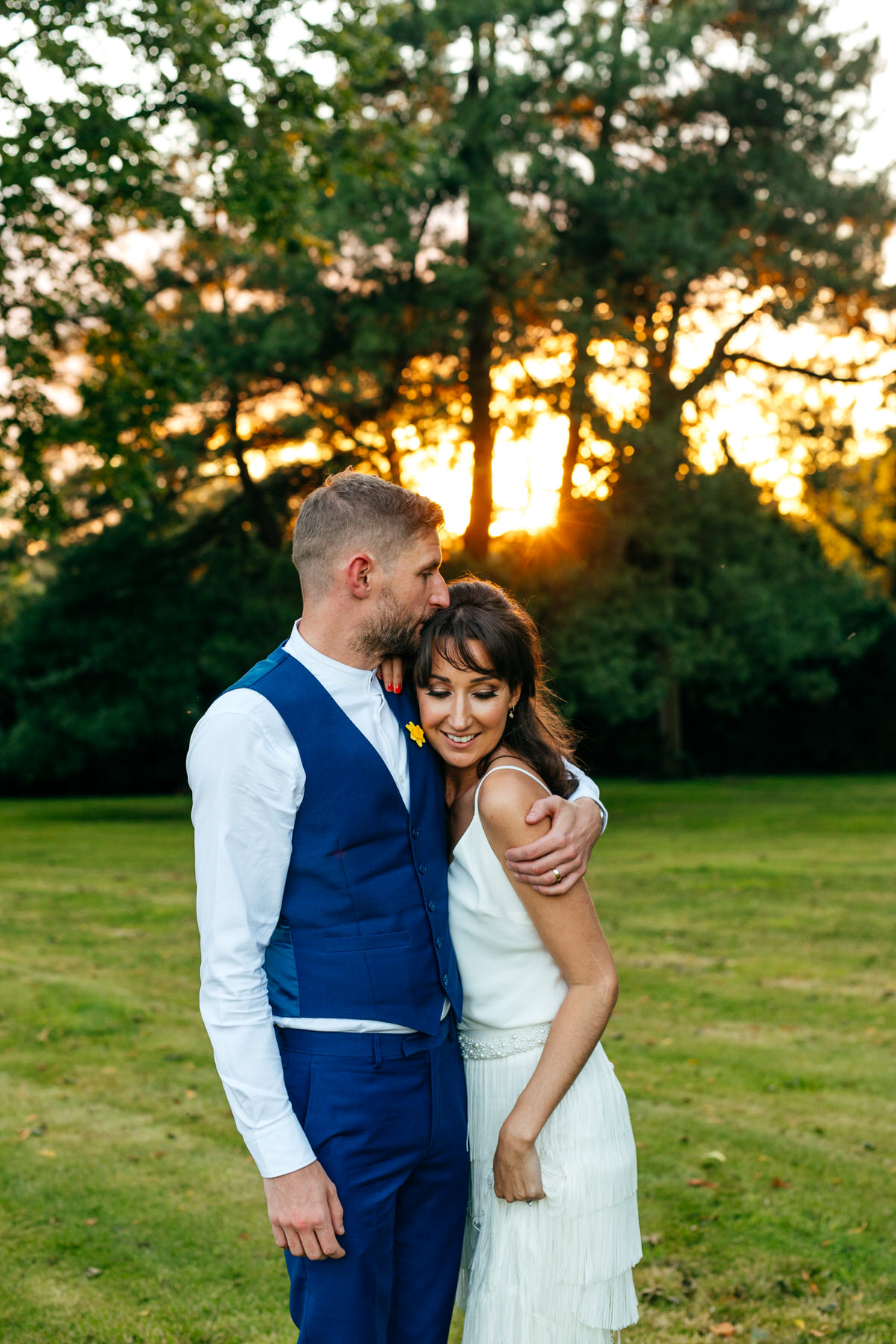 Groom kisses bride on the head during golden hour portraits