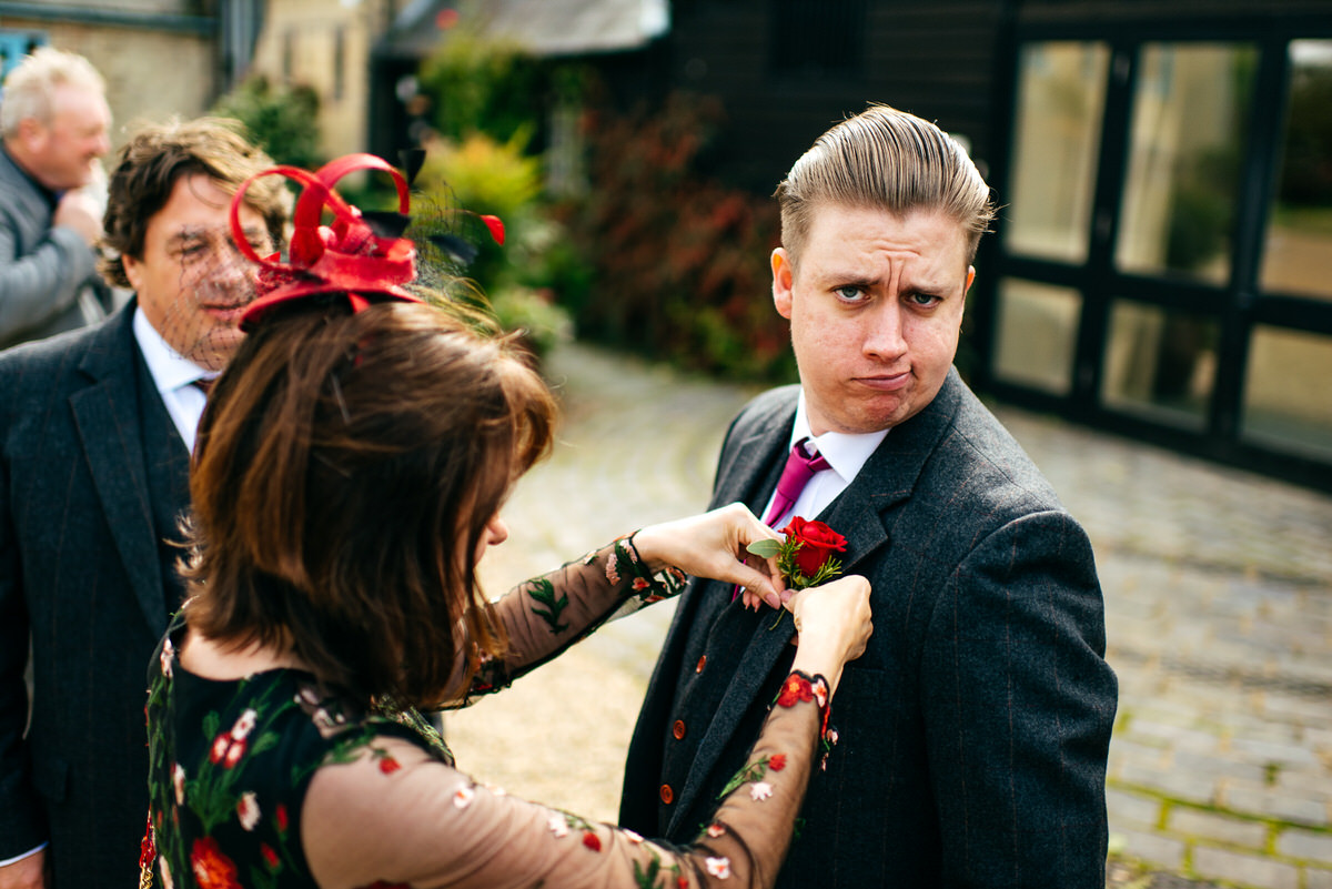 Funny faced groomsmen gets his buttonhole put on at South Farm