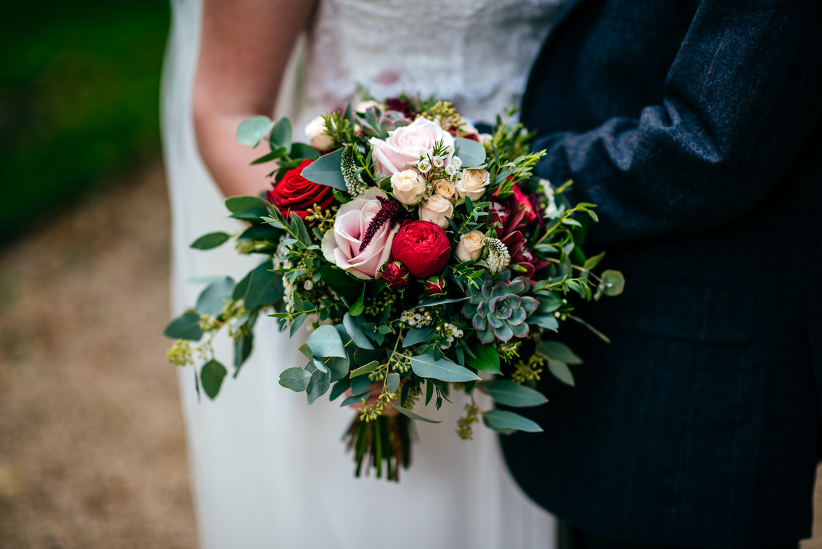 Bridal bouquet of pink and red flowers at South Farm Wedding near Royston