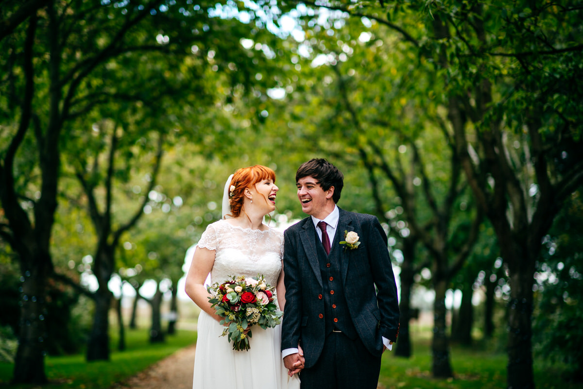 Red head bride and groom in thicket of trees at South Farm Wedding Venue laughing at eachother