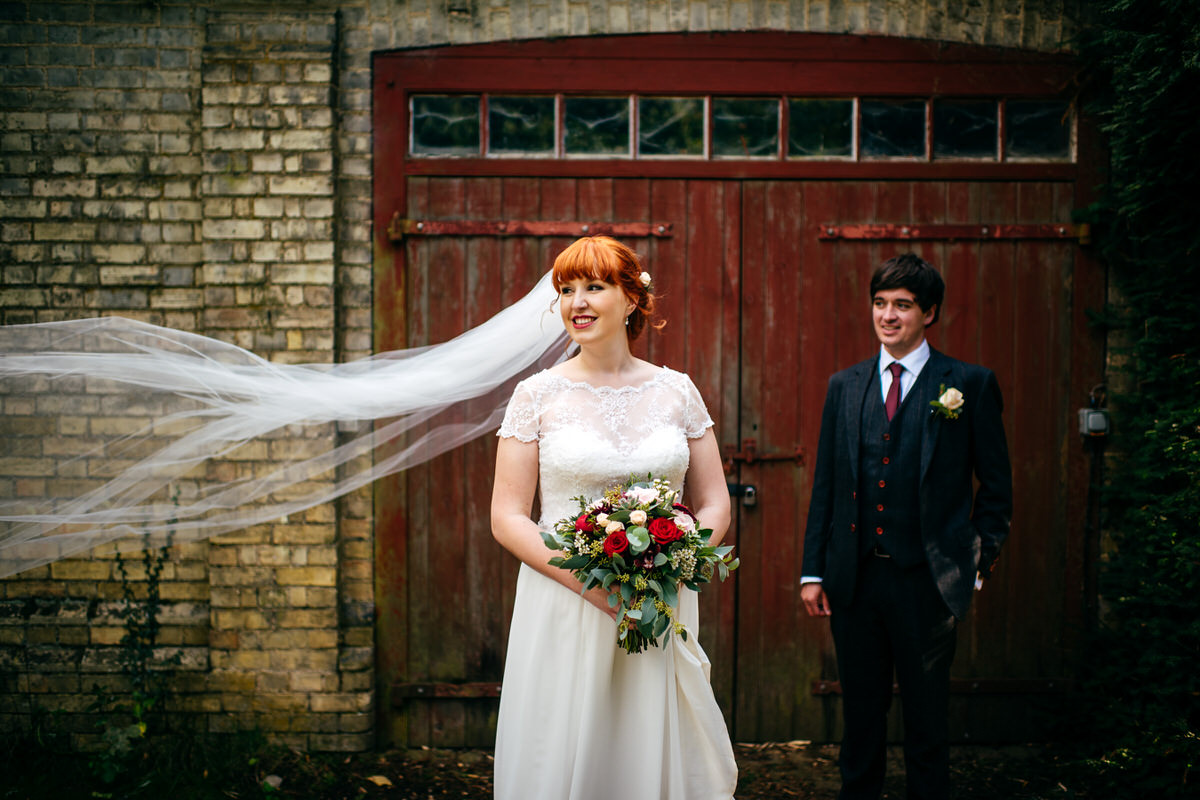 Portrait of bride and groom in front of rustic garage doors at South Farm by Jordanna Marston Photography