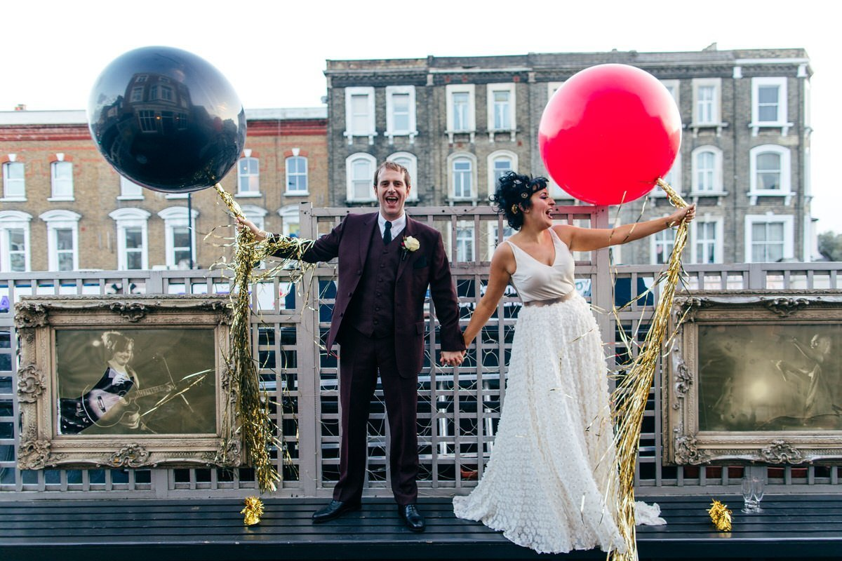 Super fun Bush Hall wedding. Couple on rooftop with balloons