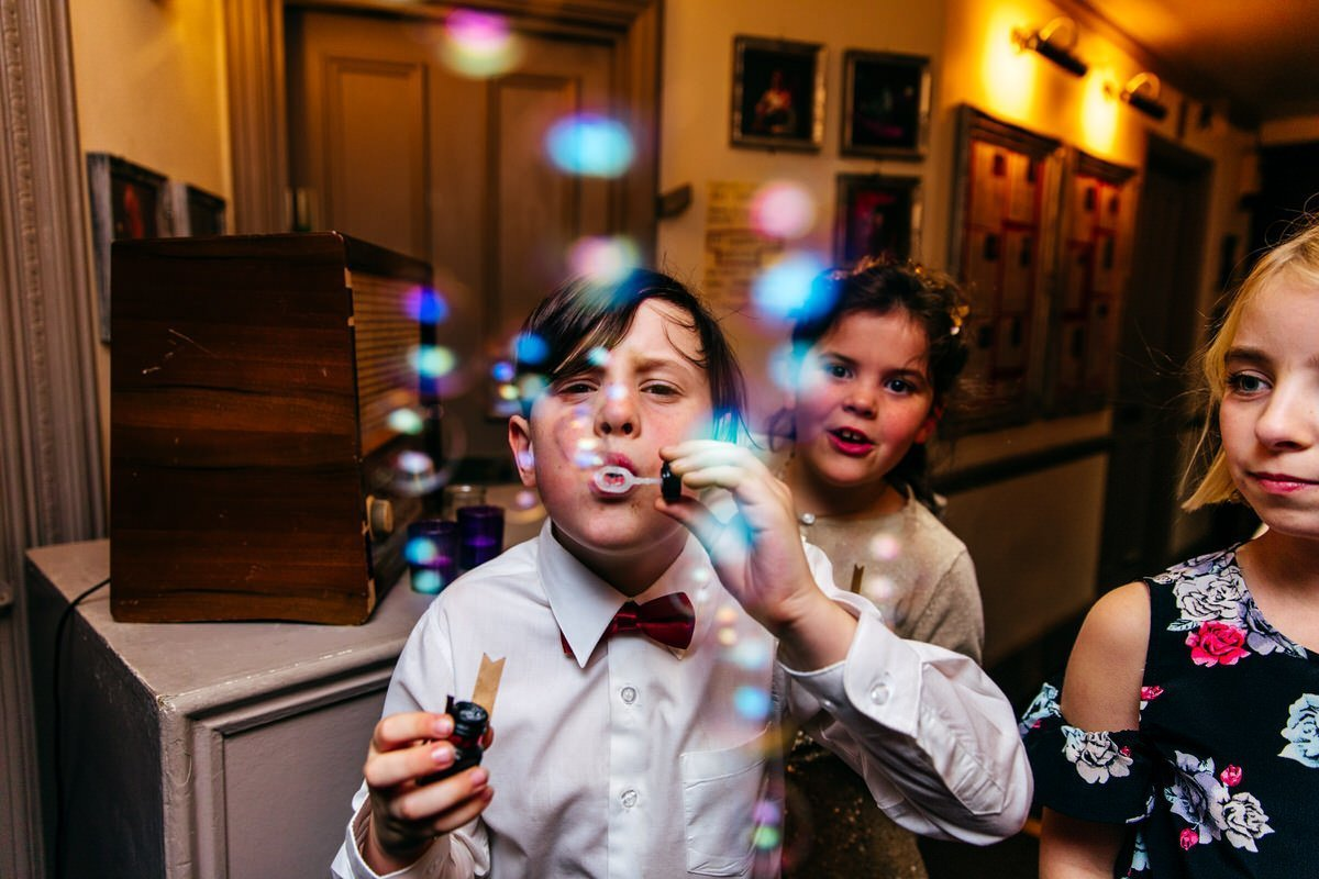 Boy blows bubbles straight at my camera at Bush Hall Wedding in London