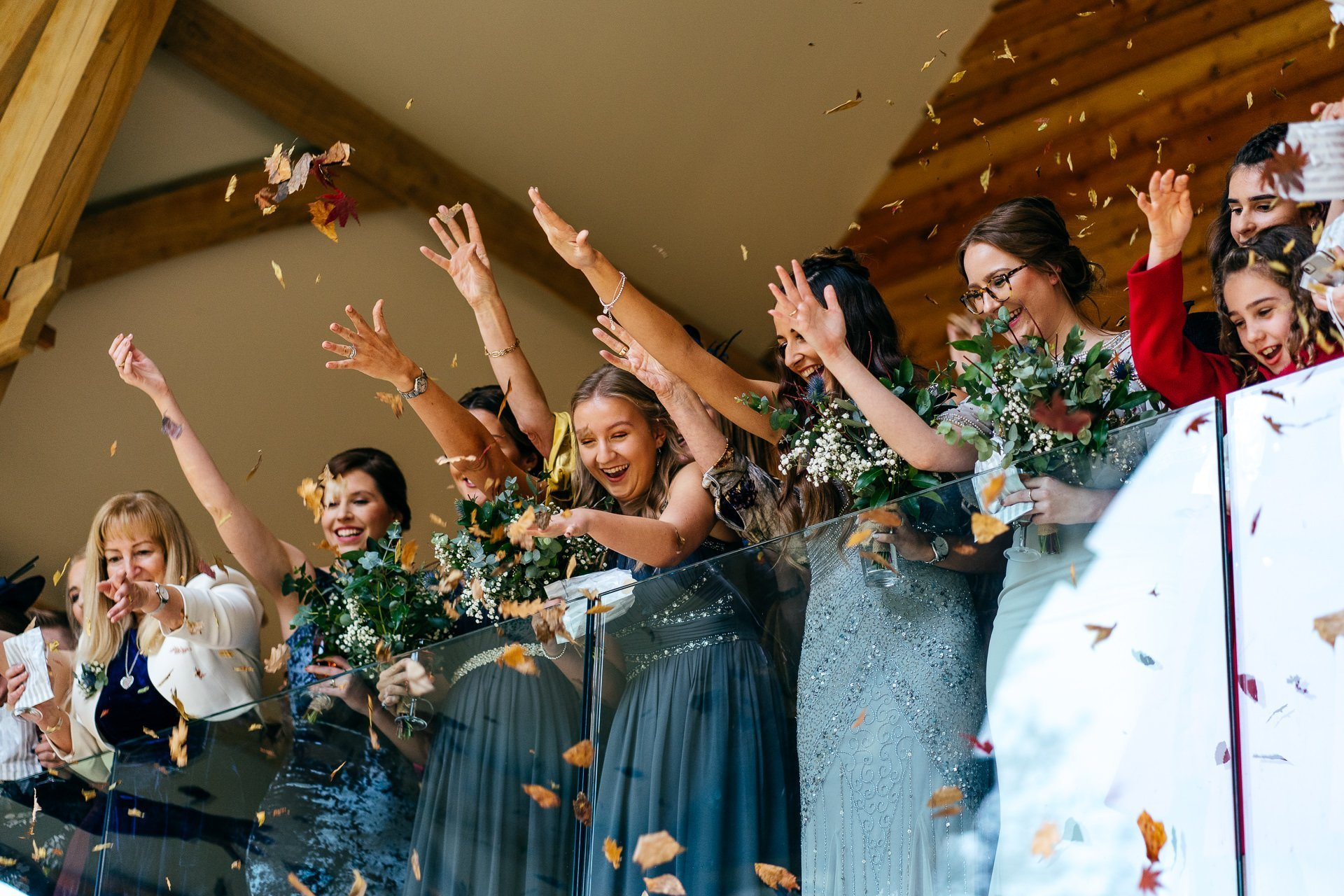 Guests throwing leaf confetti at The Mill Barns Wedding Venue Shropshire