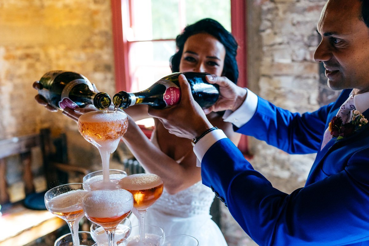 Bride and Groom pouring champagne tower upstairs at Wilton's London Wedding