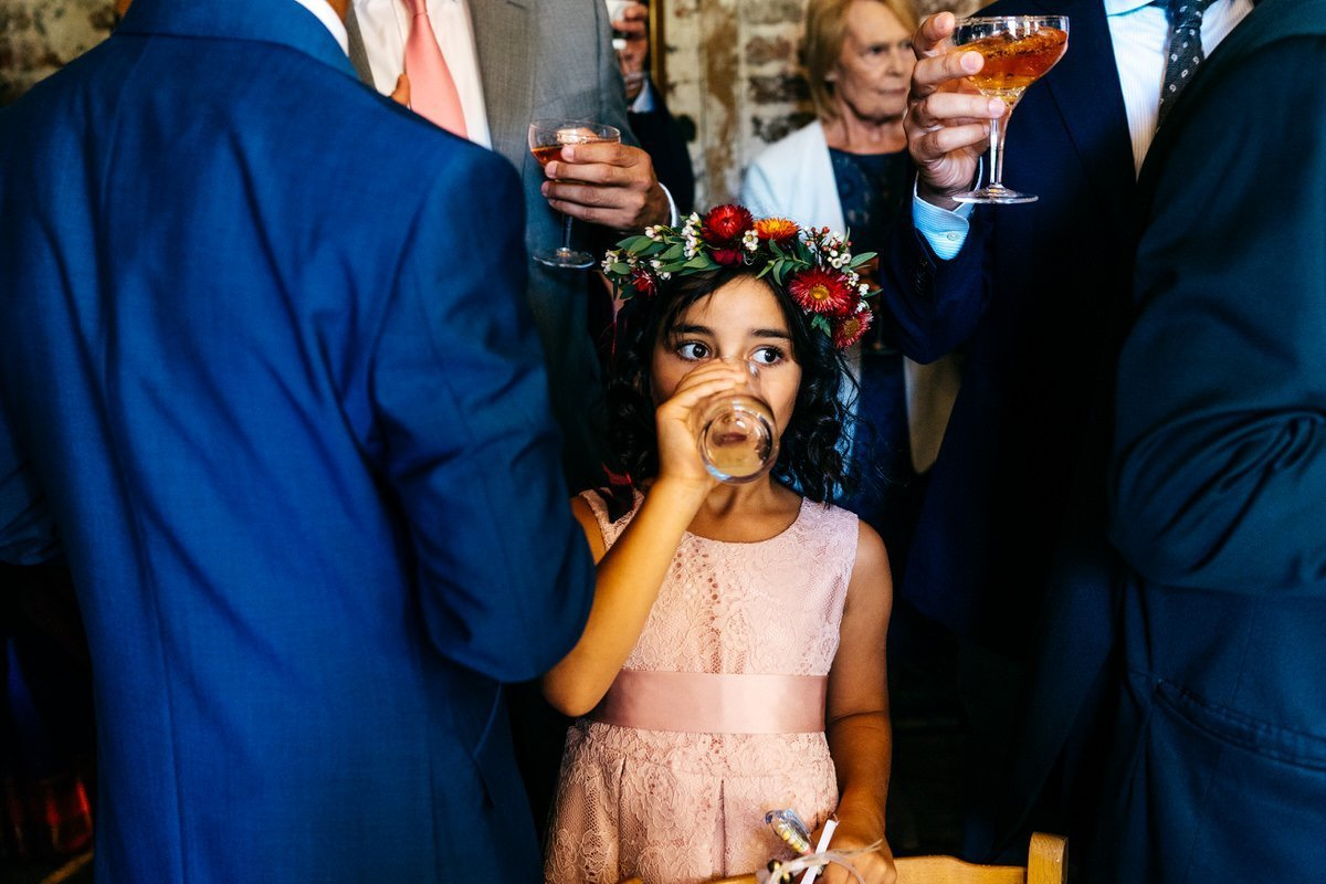 Flower girl having a drink during reception at London Wedding