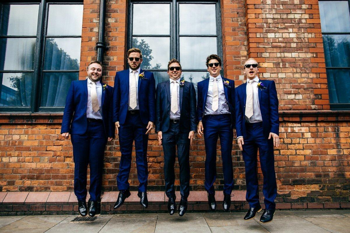 Jumping groomsmen outside Great John Street Hotel Manchester