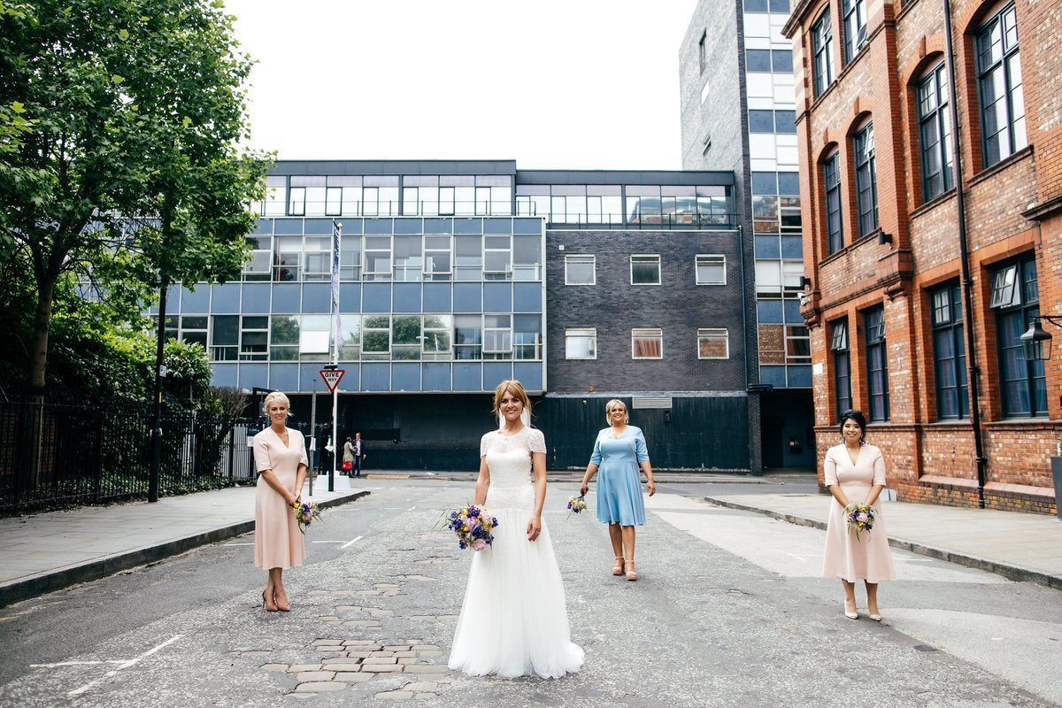 Bride and bridesmaids in street scene Manchester outside Great John Street Hotel