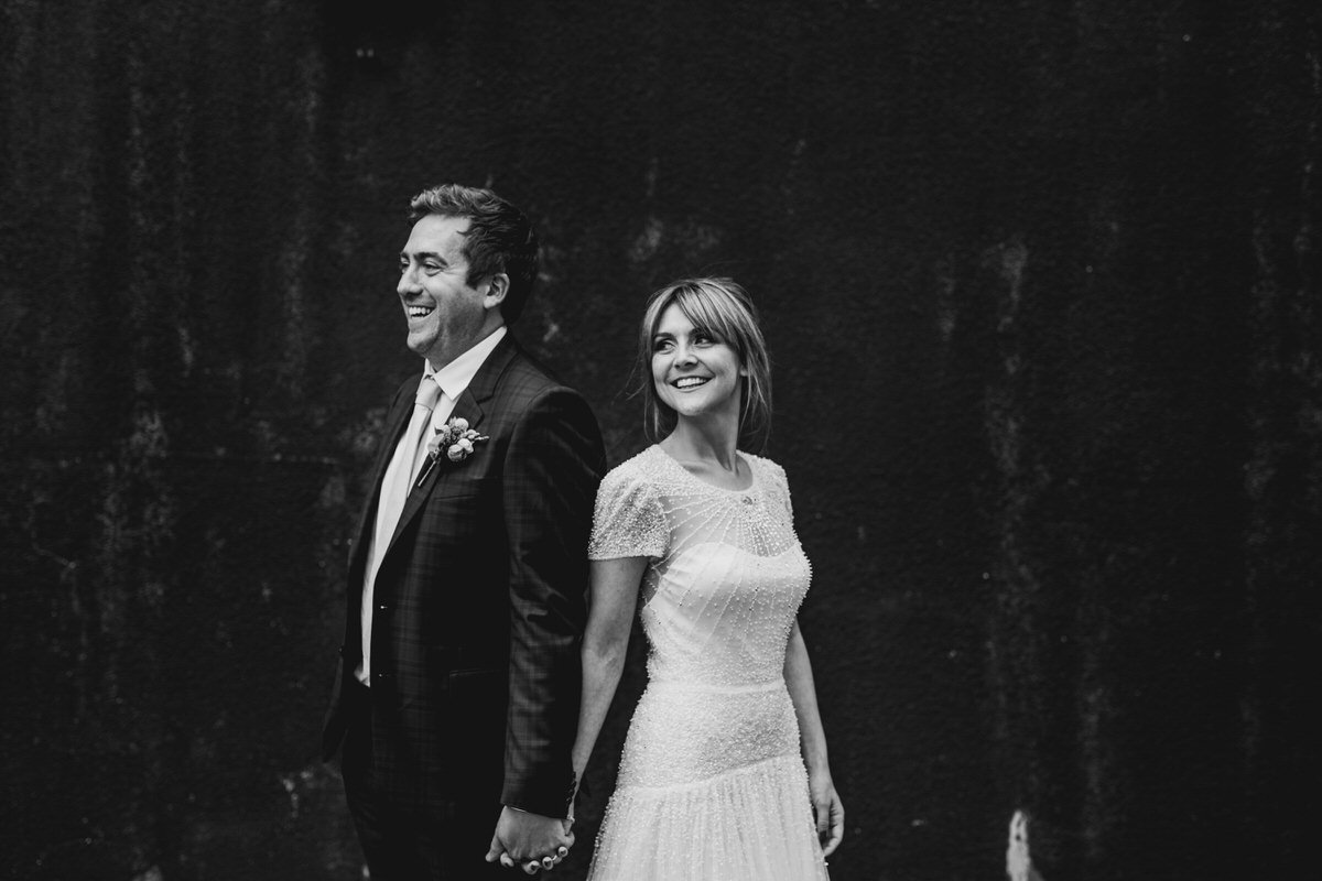 Bride and groom portrait against concrete wall
