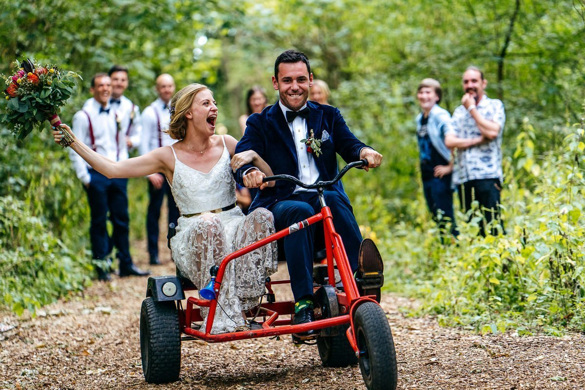 Unposed wedding photography. Screaming Bride and Groom on bike adrenaline junkies, bouquet in air
