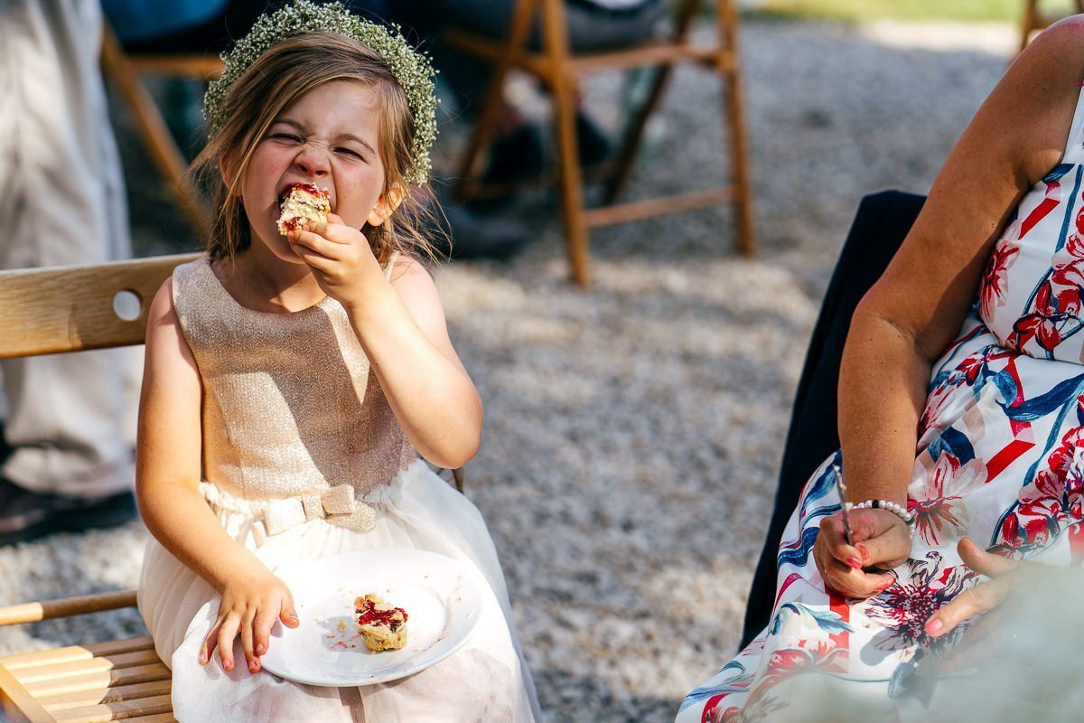 Flowergirl chomping on scone at Chilli Barn Wedding