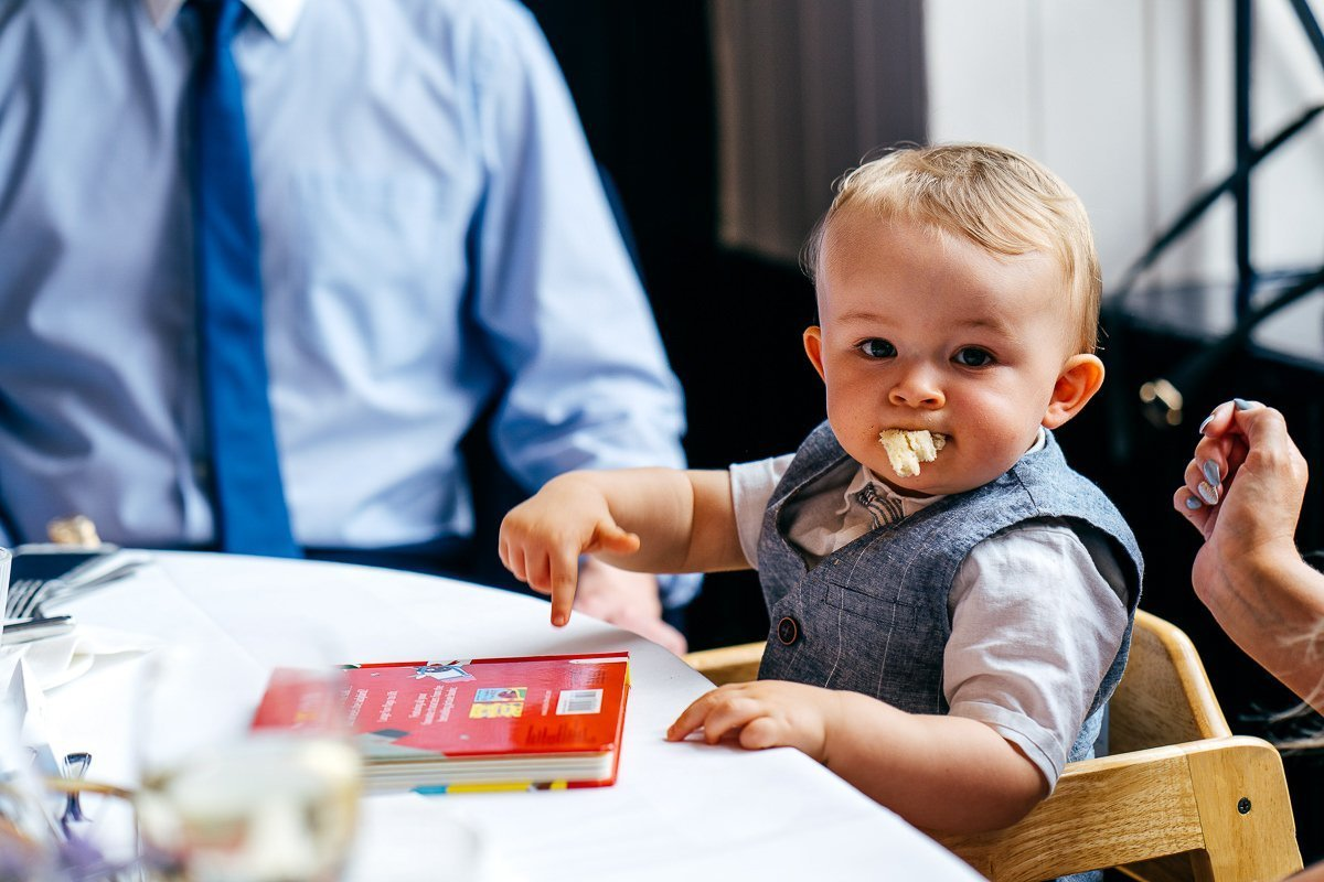 Baby in highchair with bread hanging out of his mouth