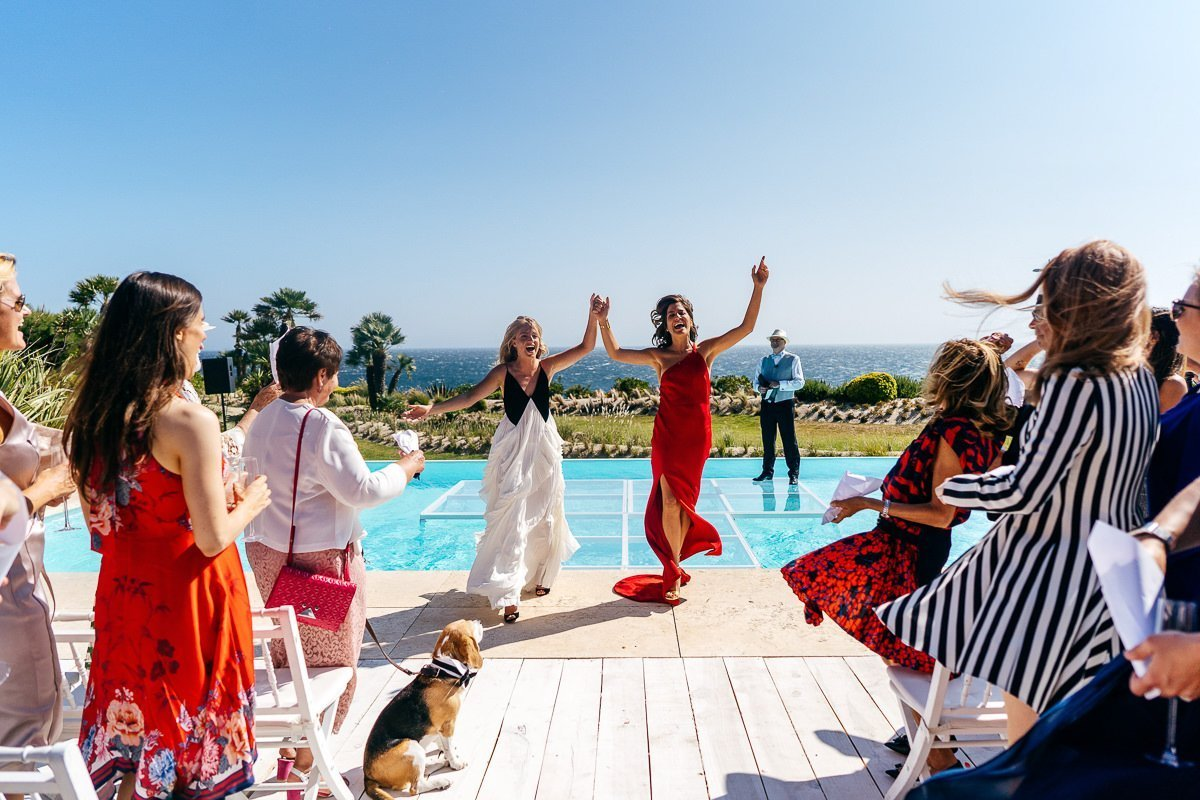 Two brides celebrating their wedding by swimming pool in Portugal. Onlooking dog.