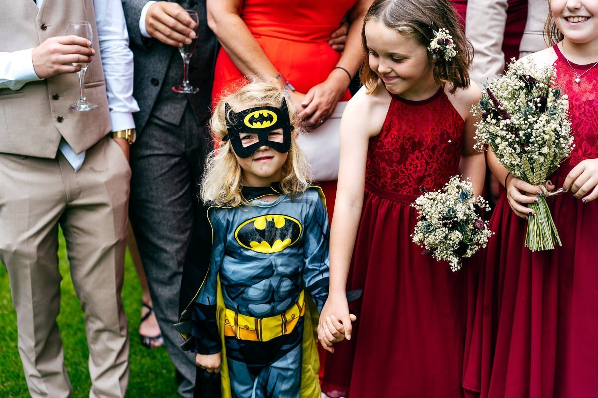Bridesmaids and batgirl in family group photo at a wedding in the Cotswolds