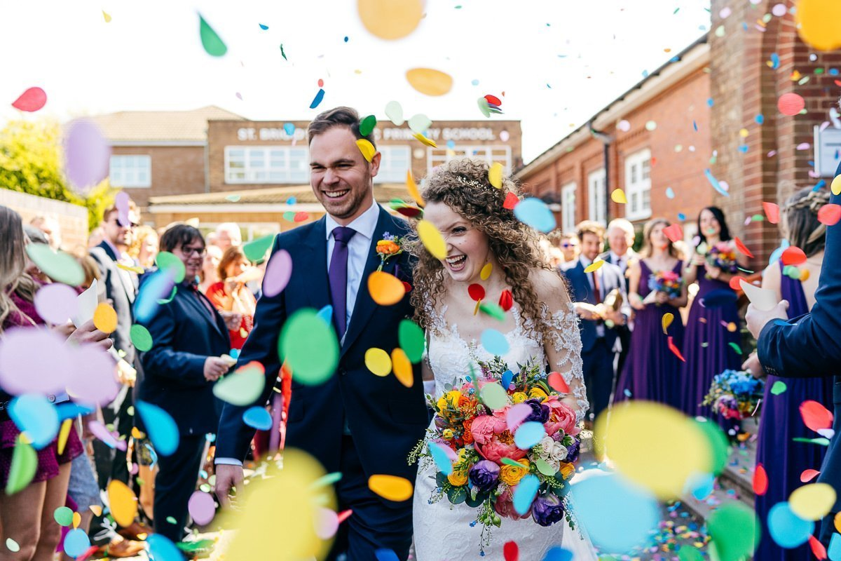 Big colourful confetti moment for couple just married coming out of church