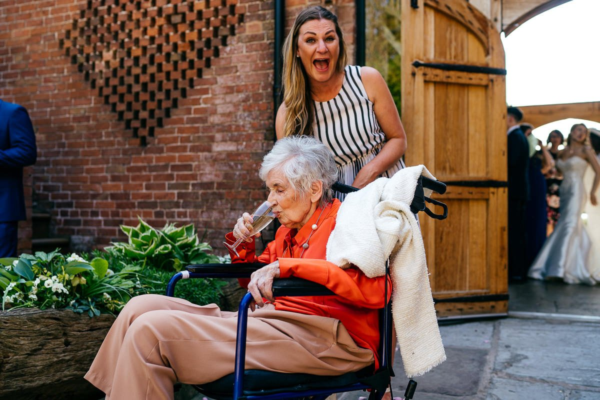 Granny in wheelchair sneaks some prosecco whilst her carer laughs approvingly