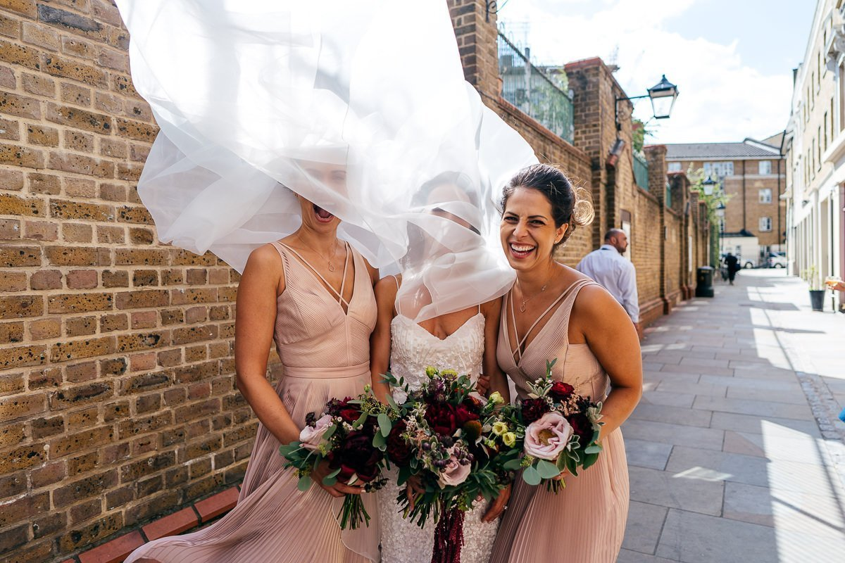 Bride veil blows over her head outside Waltons Music Hall Wedding Venue