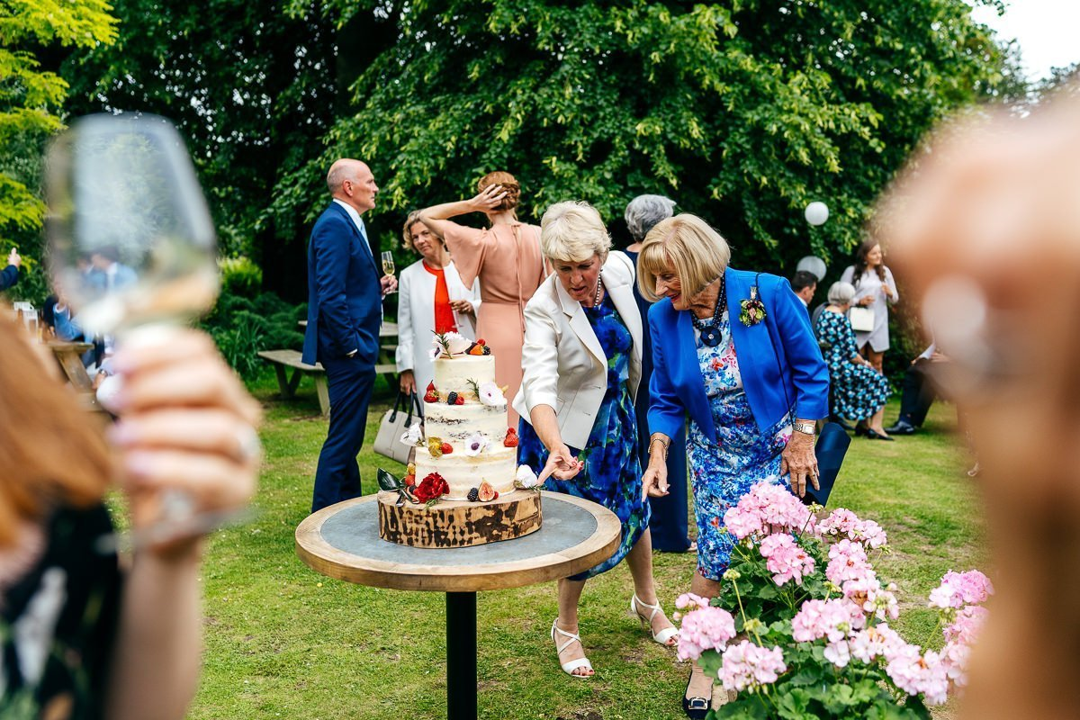 Two grandmas admire wedding cake at Wedding in Kent