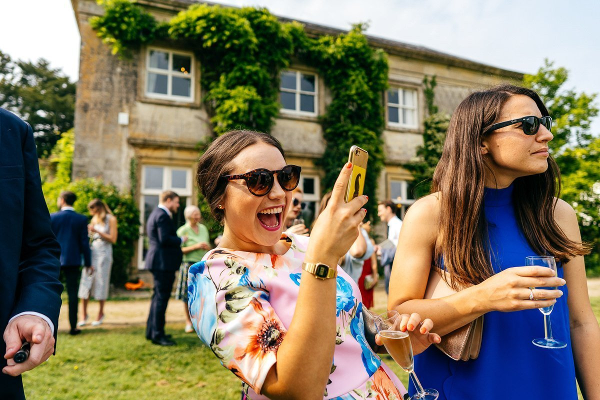 Guest laughing taking phone snap at Sparkford Hall Wedding