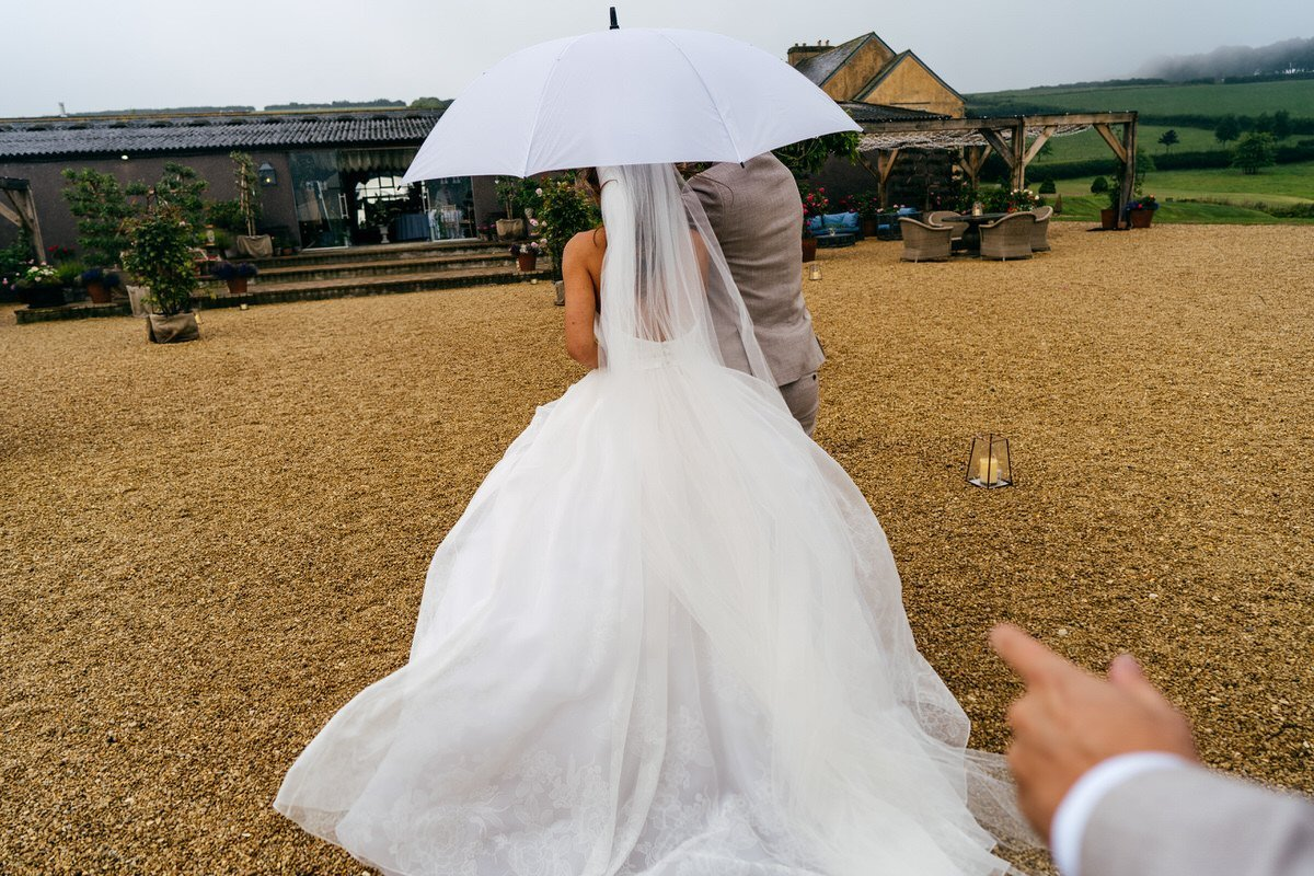 Bride Groom and Umbrella running to reception at Axnoller Party Barn