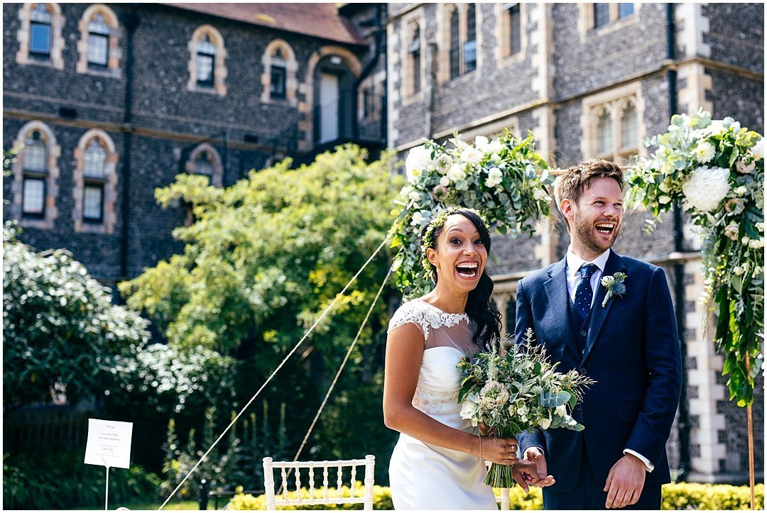 Arch of flowers and Bride wearing Suzanne Neville at Brighton College