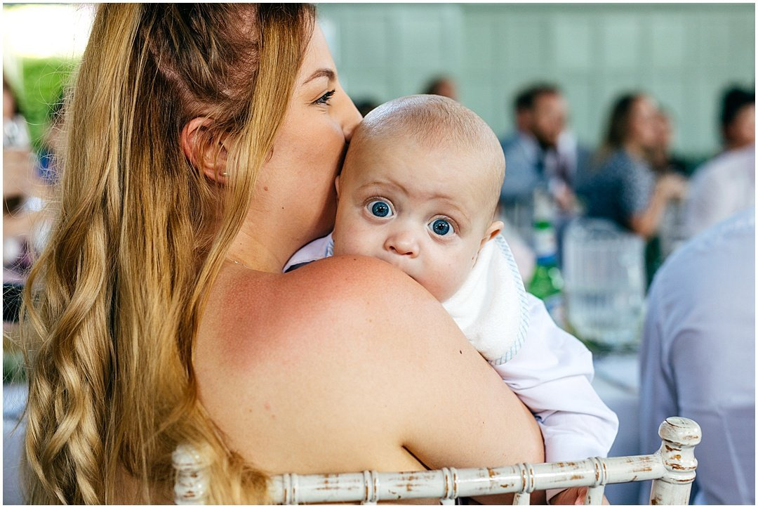 Big eyed baby stares at camera during wedding speeches at Brighton College